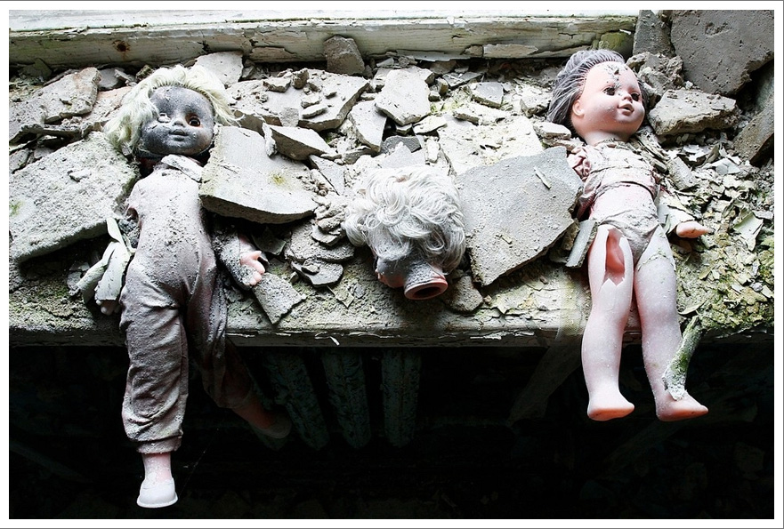 Two dusty plastic dolls and a doll's head stare blankly amid debris on a windowsill.