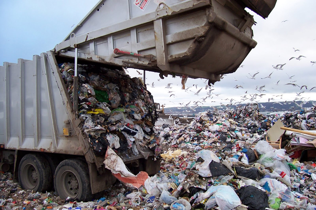 Garbage truck dumping trash into huge landfill trash piles, seagulls fly in background.