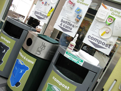 Three trash, labeled garbage, recyclables and compost; a educational poster behind each.