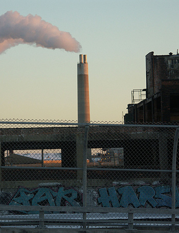 tall fence and graffitied cement overpass in foreground, tall smoking chimney in background