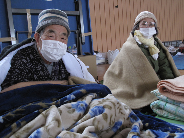 An elderly man and woman sit on floor of gymnasium covered in blankets and wearing face masks.