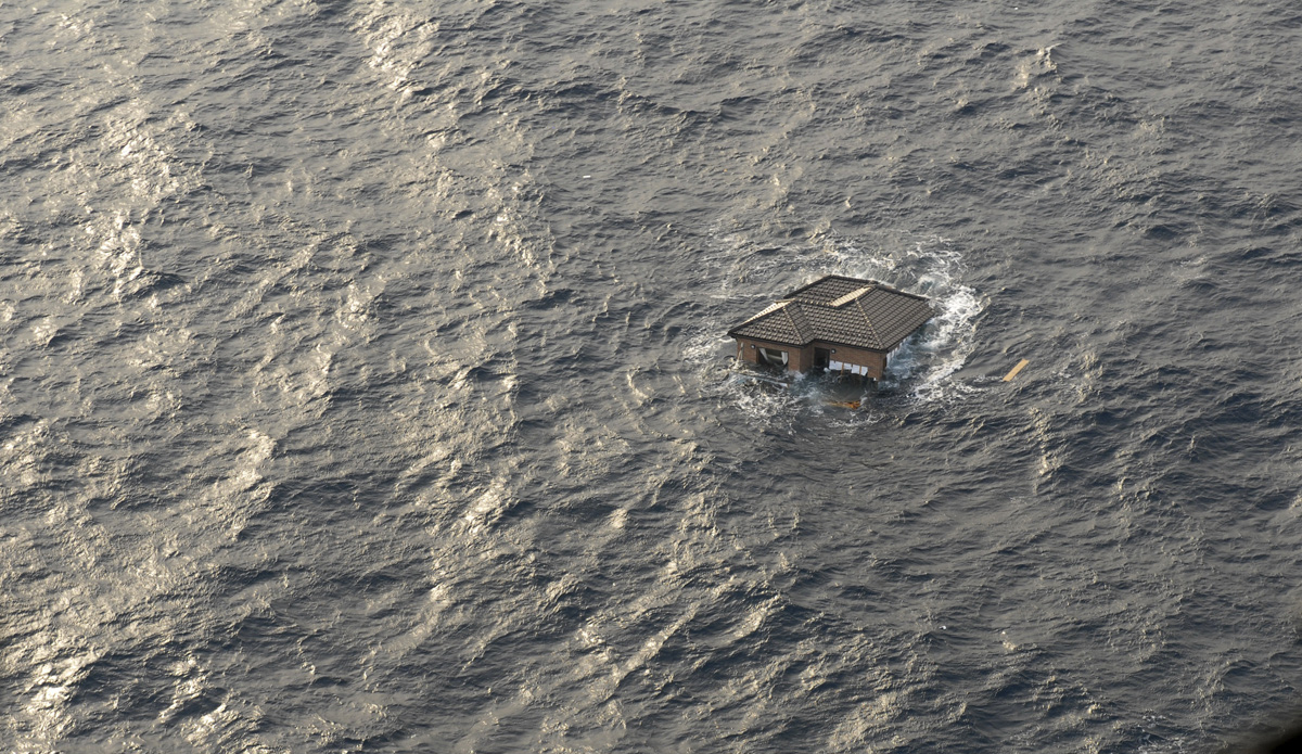 Brown house floating in open ocean.