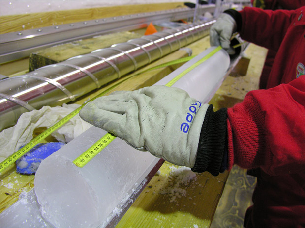 Person in red jacket and work gloves holding tape measure across a cylindrical ice core