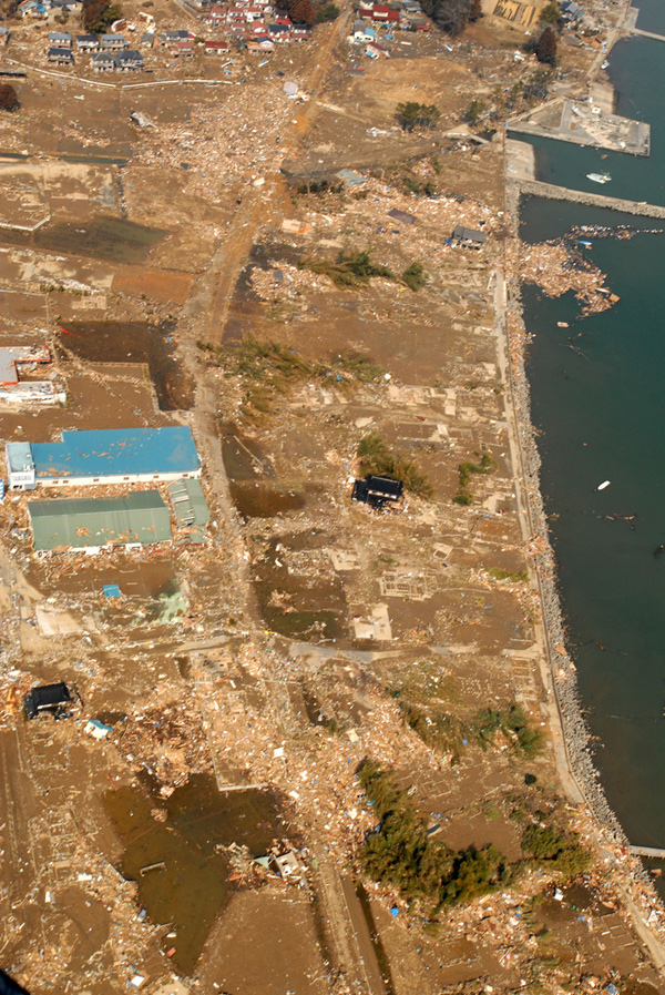 Aerial view of coastline stripped of vegetation and structures, debris scattered about.
