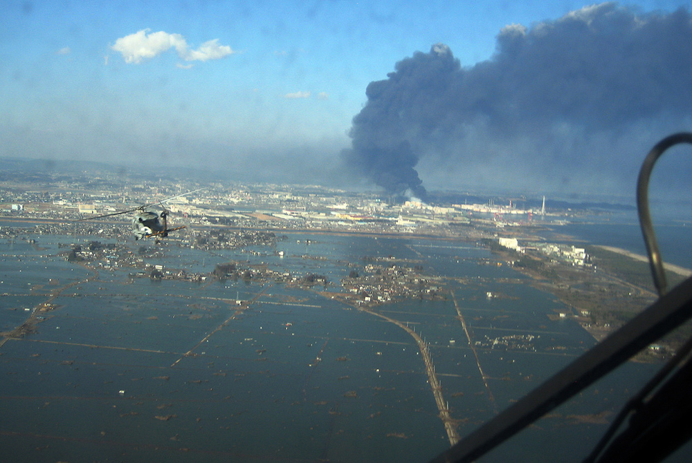Aerial view from helicopter of flooded town and large plume of smoke in air.