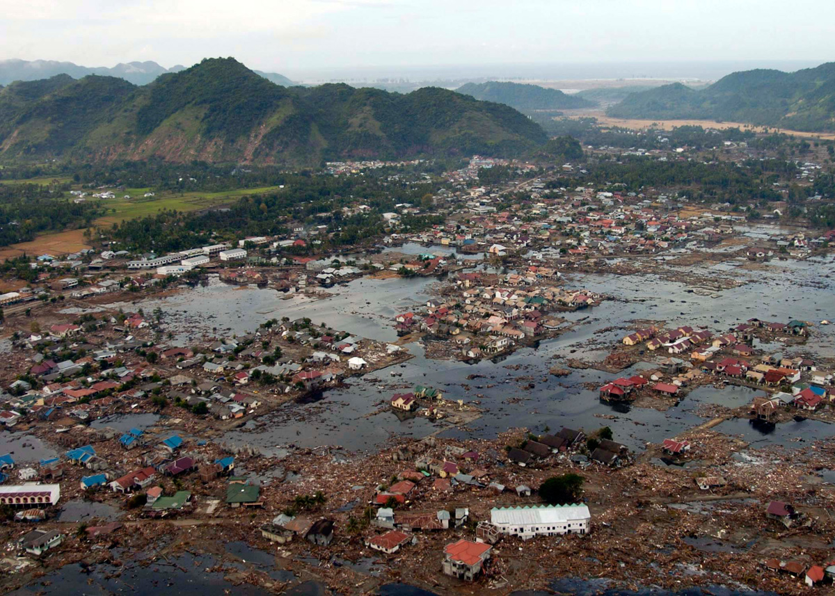 Aerial view of flooded village with debris strewn throughout, mountains surround village.