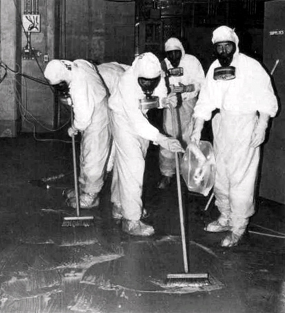 Five people in white hazard suits and face masks mop floor inside nuclear power plant.