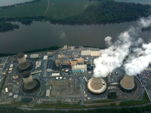 Aerial of nuclear power plant on river with 4 cooling towers, 2 of which are not working