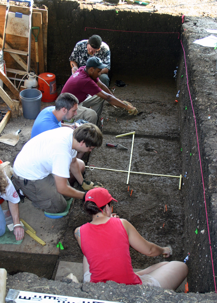Four men and one woman sitting in deep dirt pit, digging and recording with pen and paper