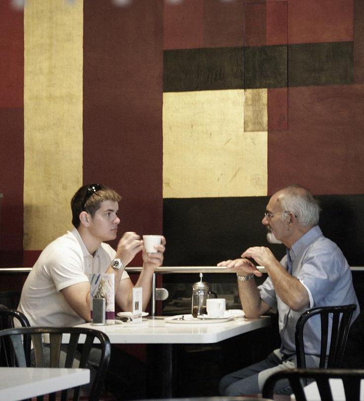 Older man and young man drink and talk at cafe table