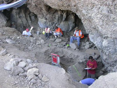 Opening of cave, three people sitting and writing, one person standing and writing, two people digging