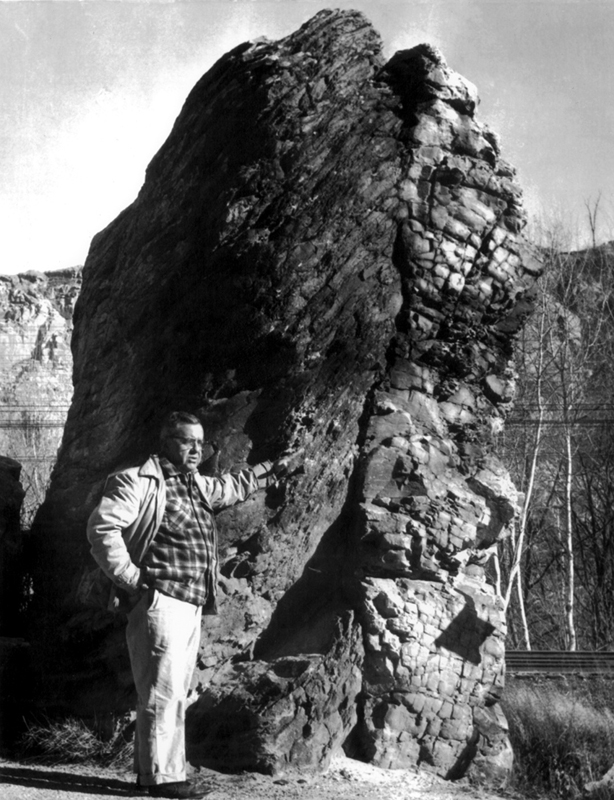 Older and slightly big man standing next to tower-like rock with his left hand resting on it