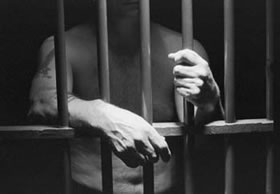 Black and white photo of shirtless man behind prison bars, hands resting on bars, face hidden.