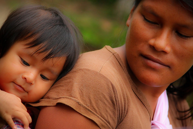 Brown skinned young mother tenderly looks at her child, whose head rests on her back