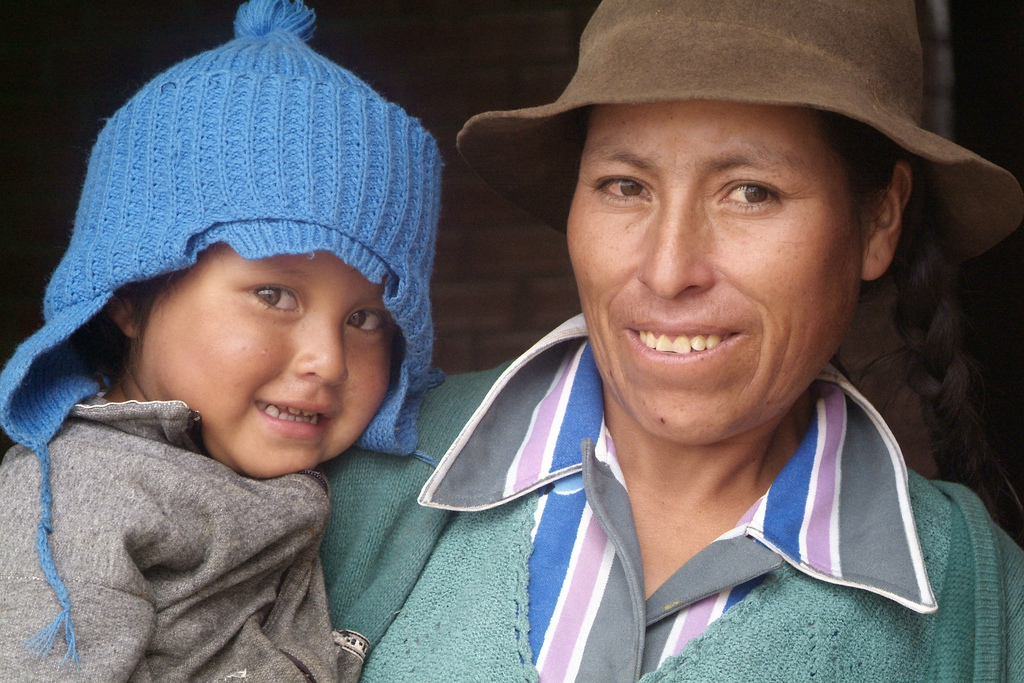 Brown skinned mother holding her baby to her side, both wearing hats and smiling into camera.