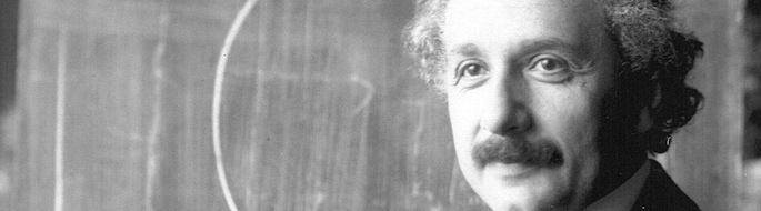 Black and white photo: closeup of Einstein's face with blackboard in background
