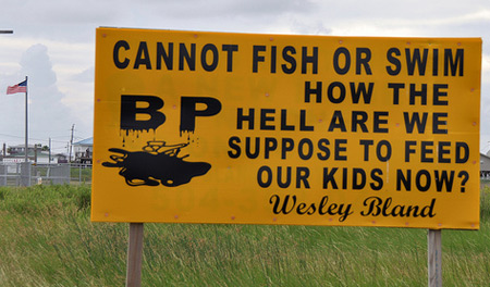 Yellow sign on road says 'Cannot fish or swim how the hell are we suppose to feed our kids now?'