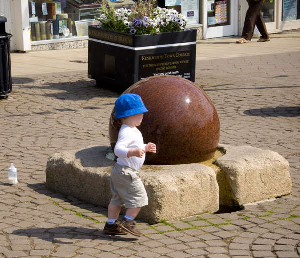 Young person prances around a spinning ball of stone in a park