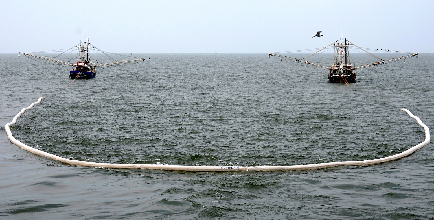 Two boats with long mechanical arms float side-by-side on the ocean tugging a floating oil boom