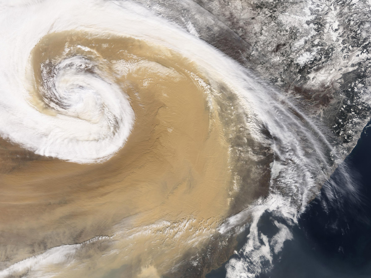 Satellite image of huge cloud swirl mixed with dark tan dust swirl over land mass