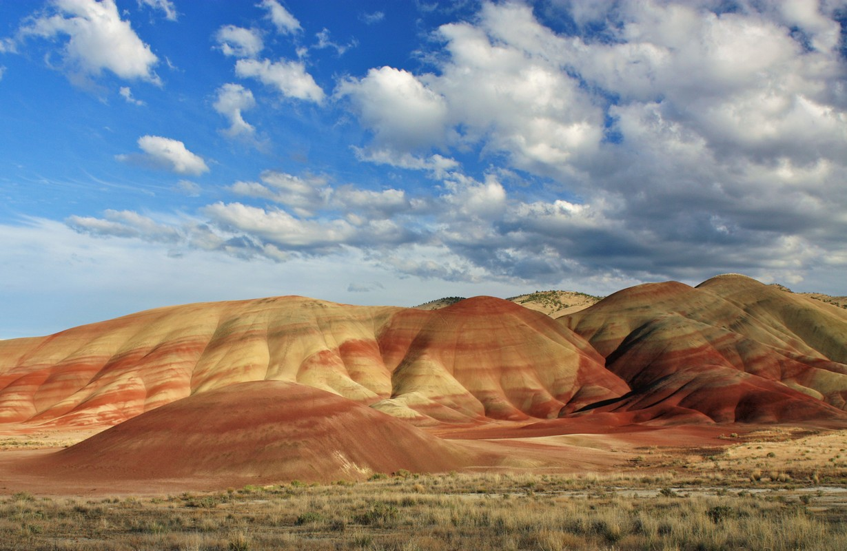 Set of barren, rugged hills with tan and red layers on a clear day with puffy white clouds in sky.