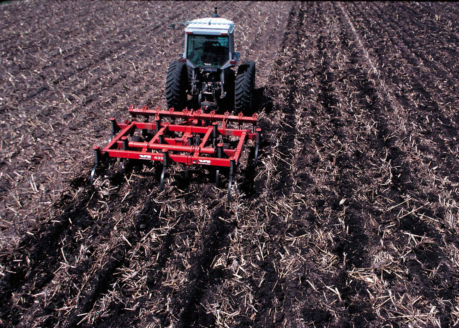 tractor pulling small plow through dirt field covered in plant debris