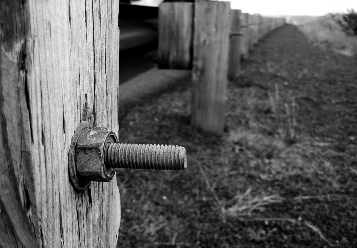 Rusty screw and nut in weathered fence post, fence continues along barren dirt, blurs into background