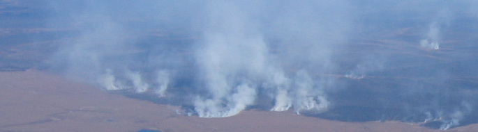 line of fires seen as thick barrier of smoke along tundra landscape
