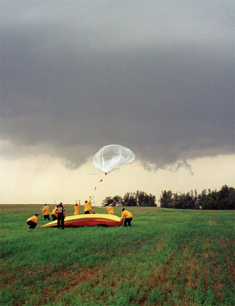 Nine people wearing yellow jackets in field launching balloon with instruments into clouded sky