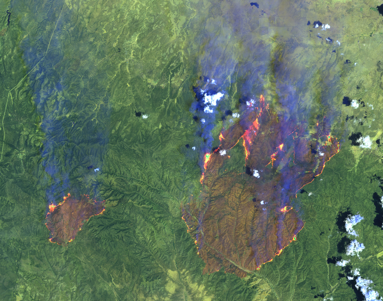 Satellite image of green mountains. Fires are large and small smoking, pink-orange patches.