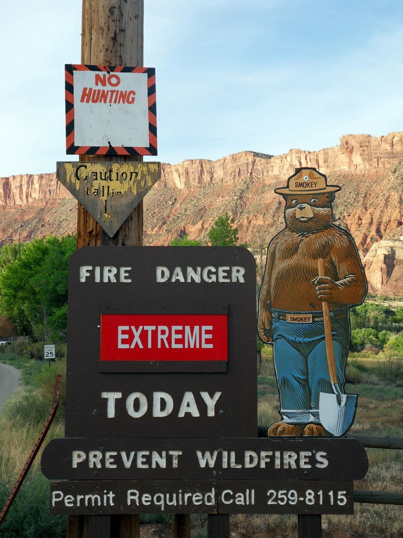 Wooden fire danger sign with cartoon bear dressed as park ranger, sign cautions extreme danger