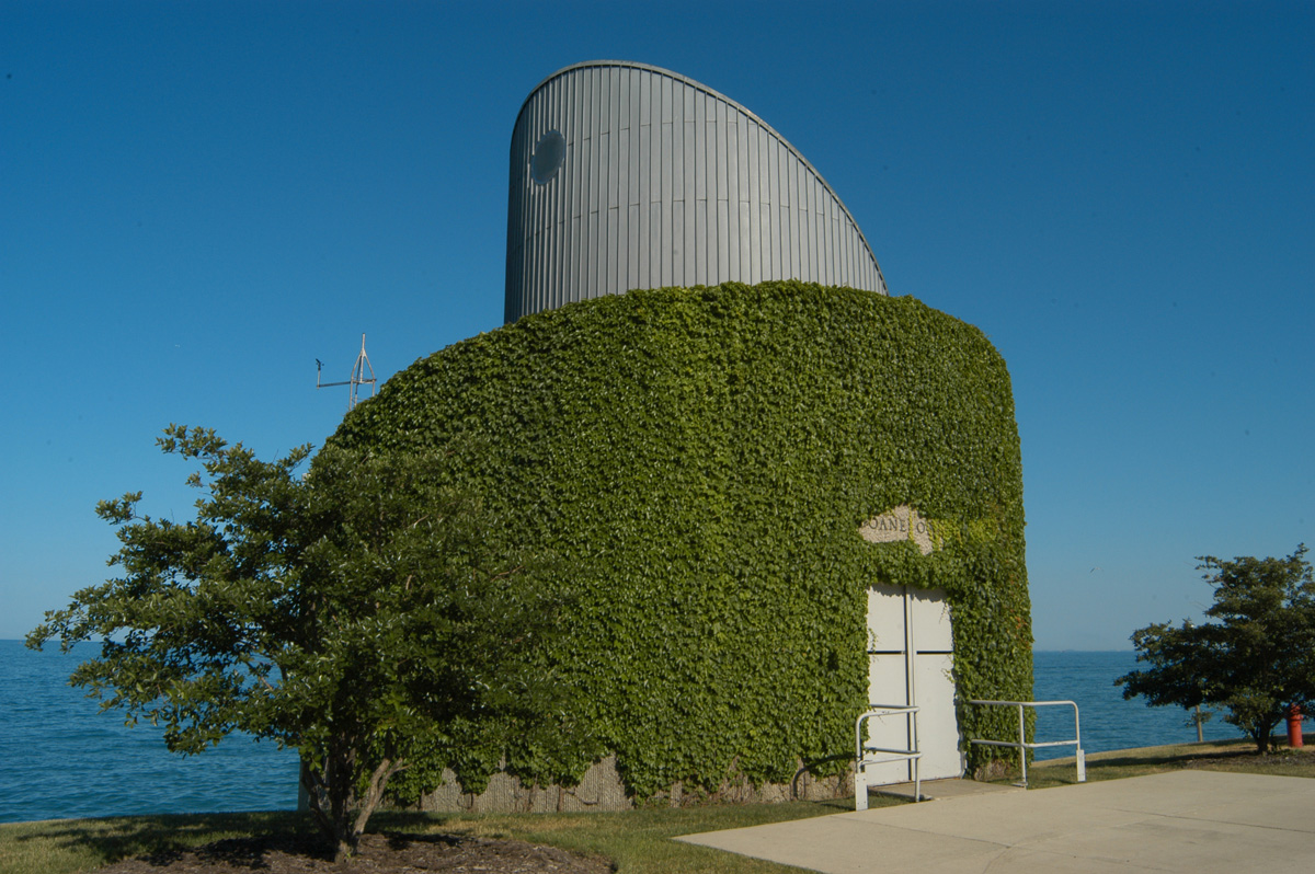 Circular building covered in green ivy with curved protrusion on its roof on lake shore