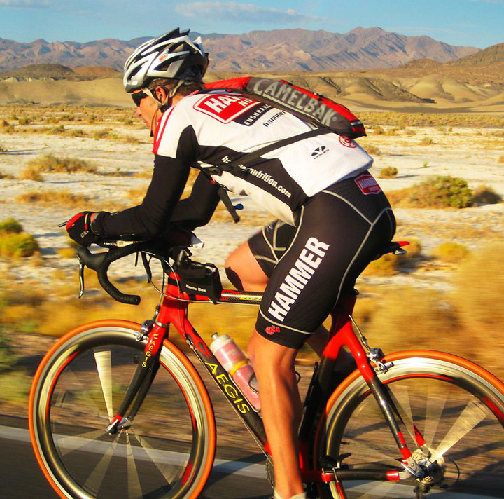 Man wearing cycling clothes rides across a desert