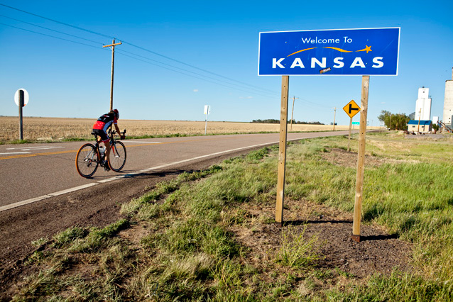 Cyclist on country road, open field on one side, 'Welcome to Kansas'; sign on other