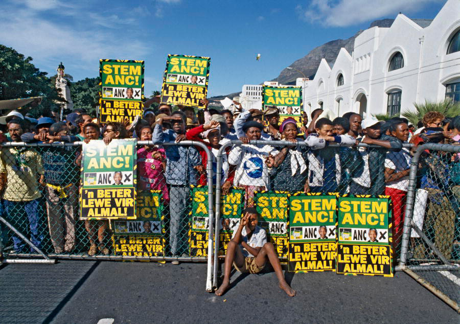 Dozens of Africans stand behind fence, several people hold up posters with Afrikaans words on them