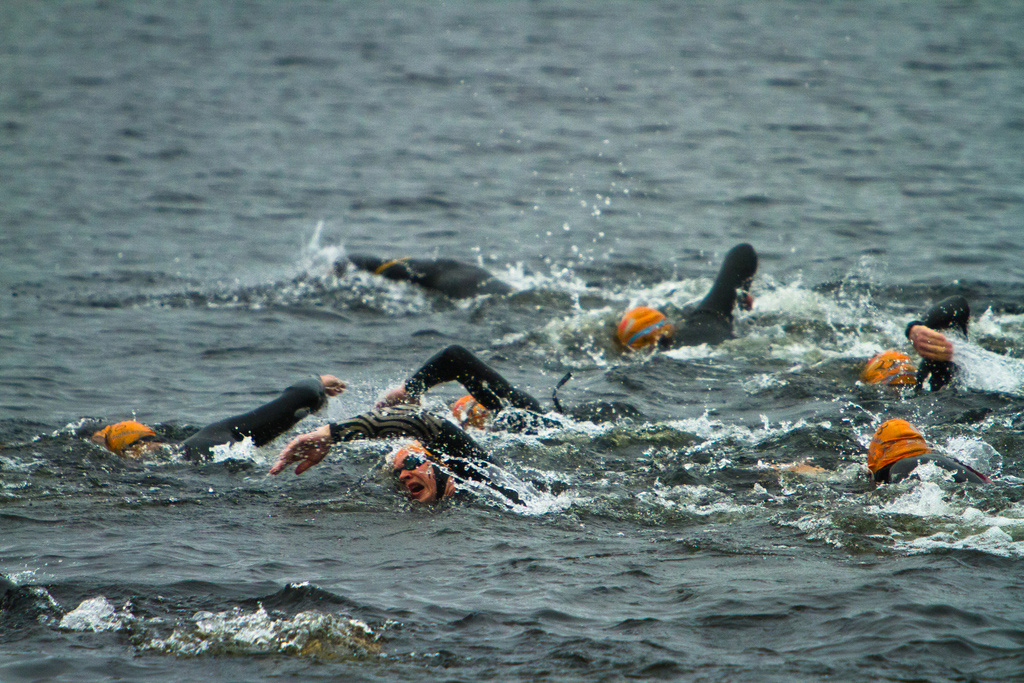 Seven people wearing wet suits and goggles swimming in dark water