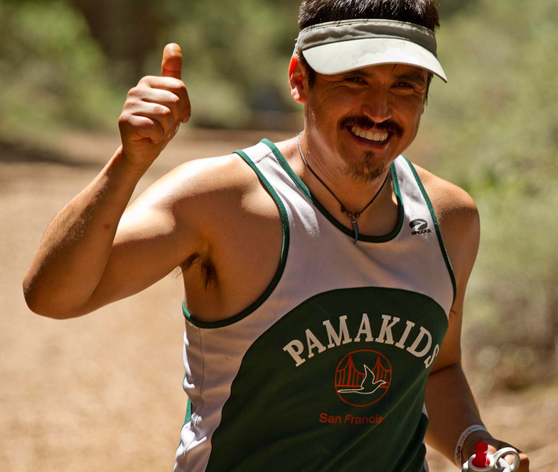 Runner with mustache and goatee wearing visor and green tank smiles and gives thumbs up