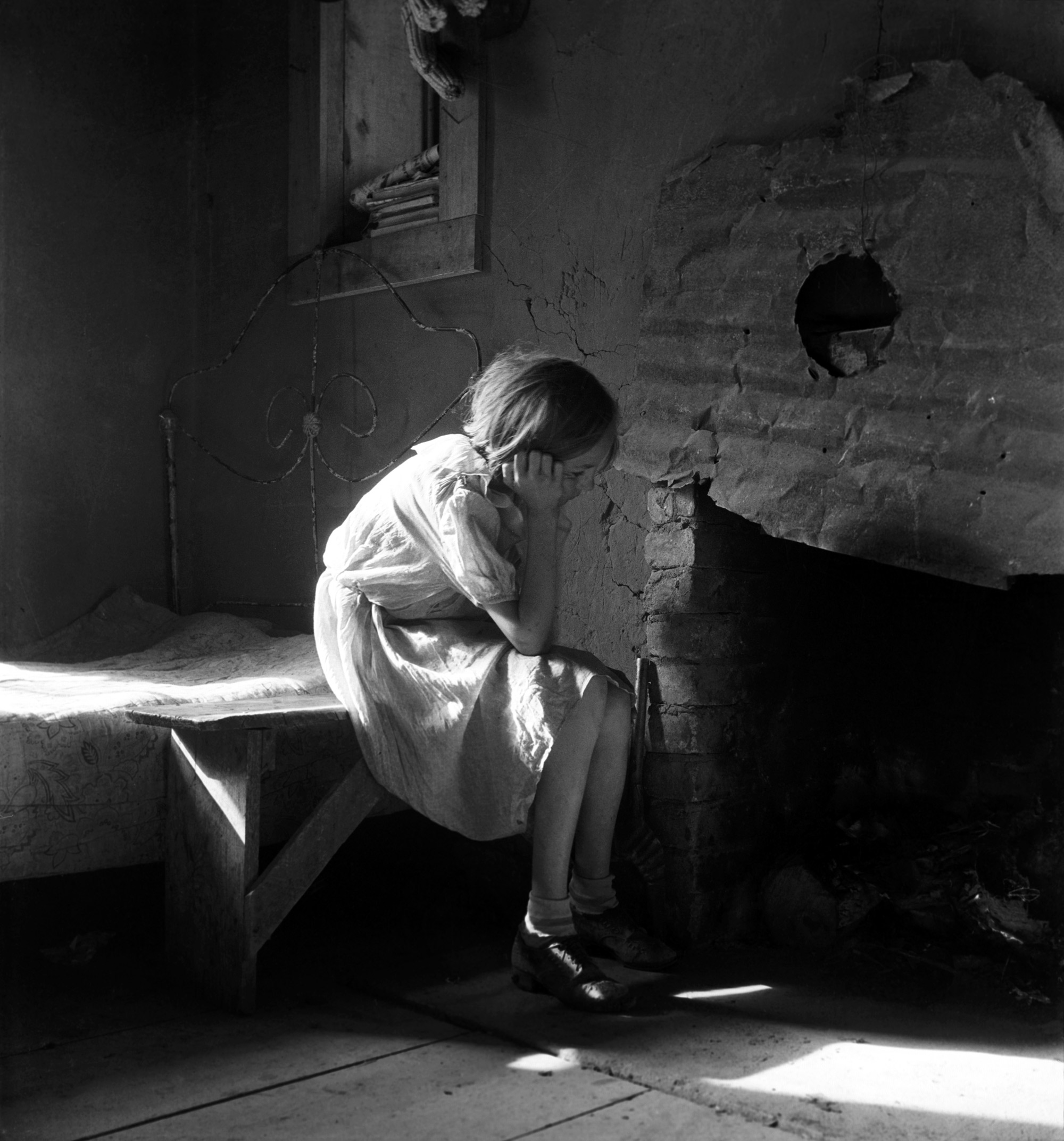Young girl in 1930s garb sits on a bench in a bedroom, looking sadly into the fireplace
