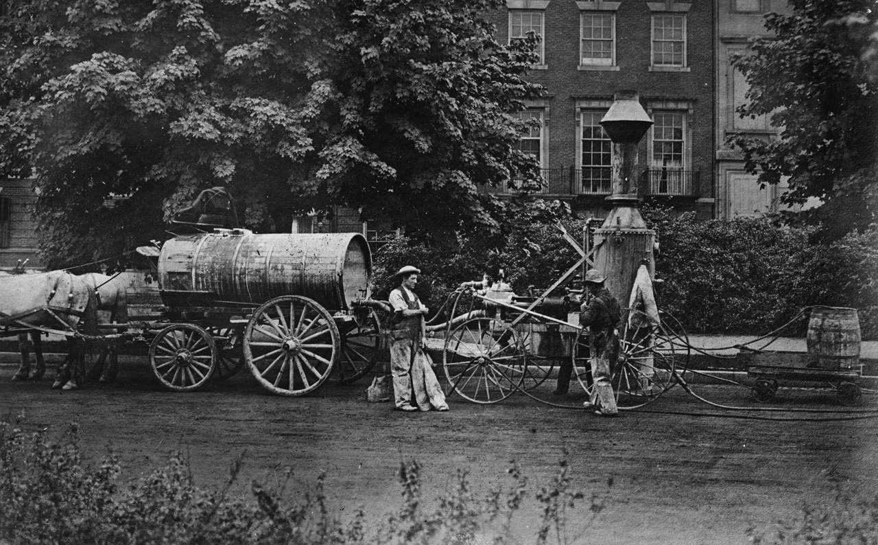 Two men with horse-drawn tank and upright heater-sprayer in front of a brick house