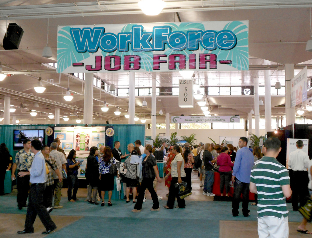 Dozens of people mill around booths at a convention center, sign hangs from ceiling