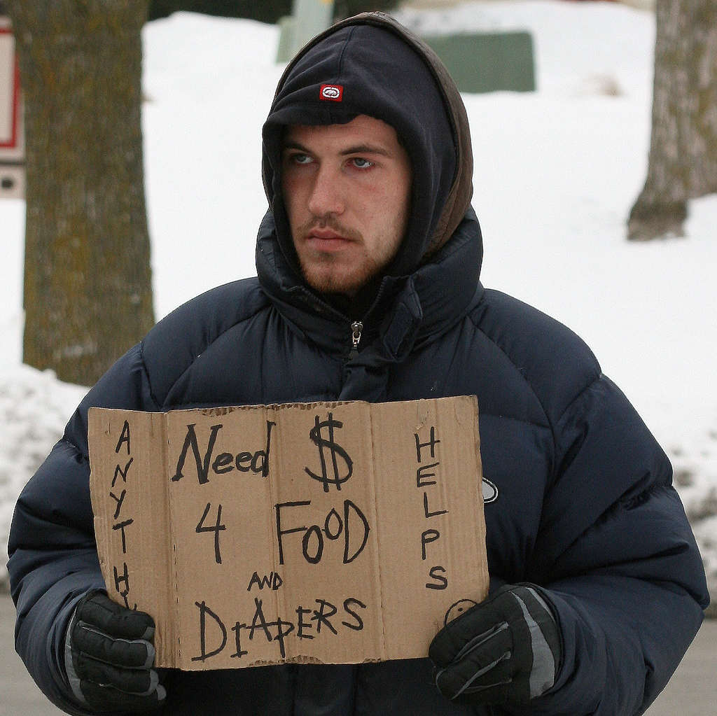 Man bundled in winter coat holds cardboard sign that says need money for food and diapers