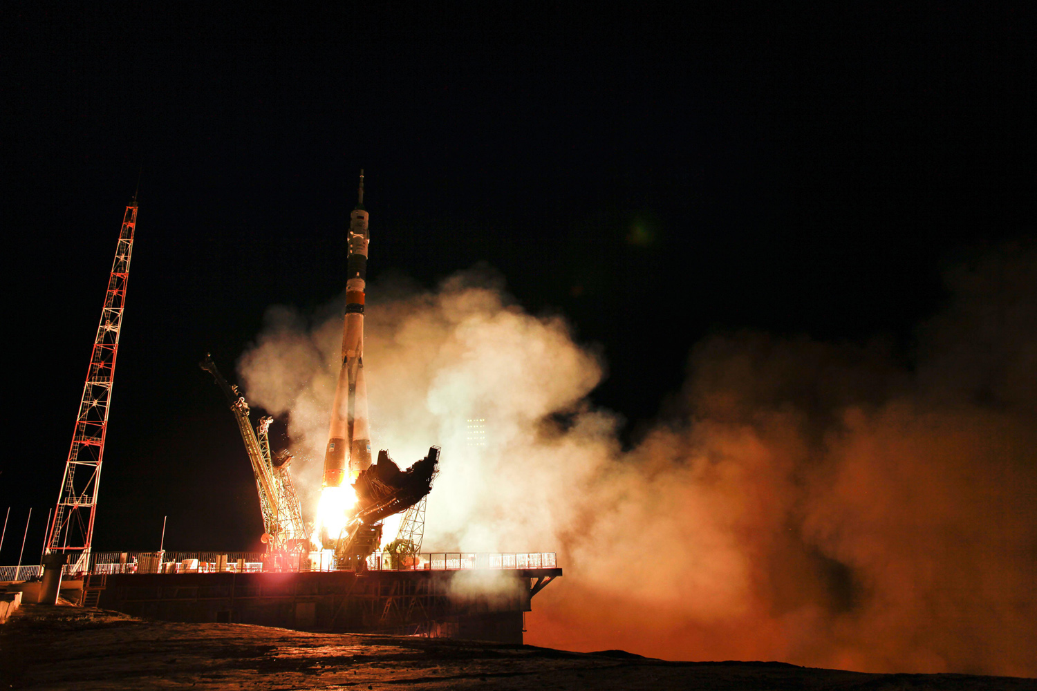Rocket launches from platform at night, bright orange flame and huge smoke plume