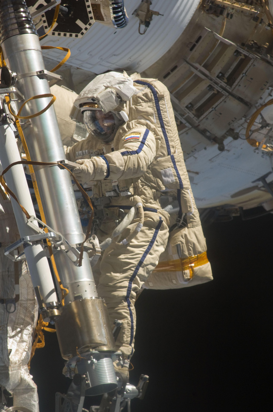 Astronaut in space suit holds a metal cylinder outside space station, seen in background