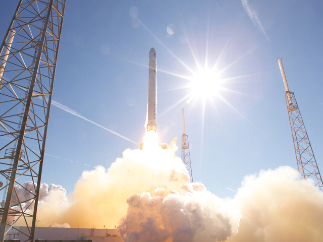 Thin rocket launches into sunny sky, creating large smoke plumes