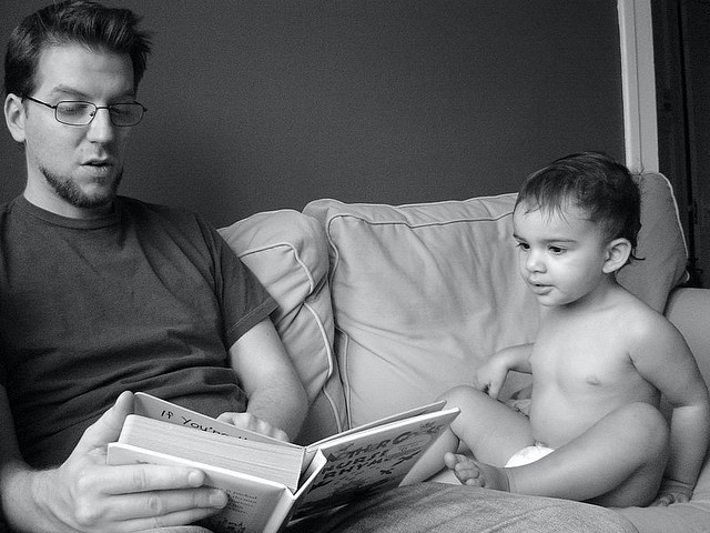 Man wearing glasses reads book to diaper clad baby, both sit on a couch