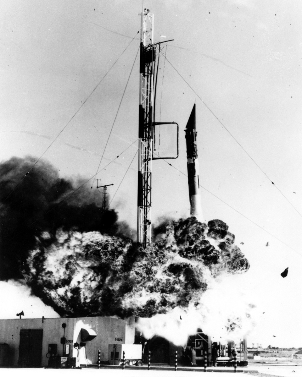Black and white photo of a skinny rocket launching with an explosion plume at its base