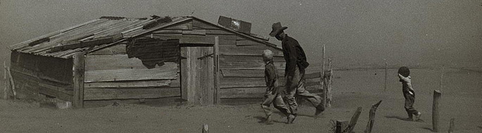 black and white dustbowl era photo of farmer and children and sand-covered shack
