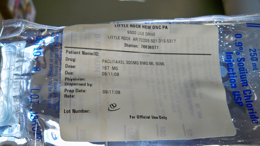 Intravenous bag partly full with clear liquid; sticker shows patient and dose
