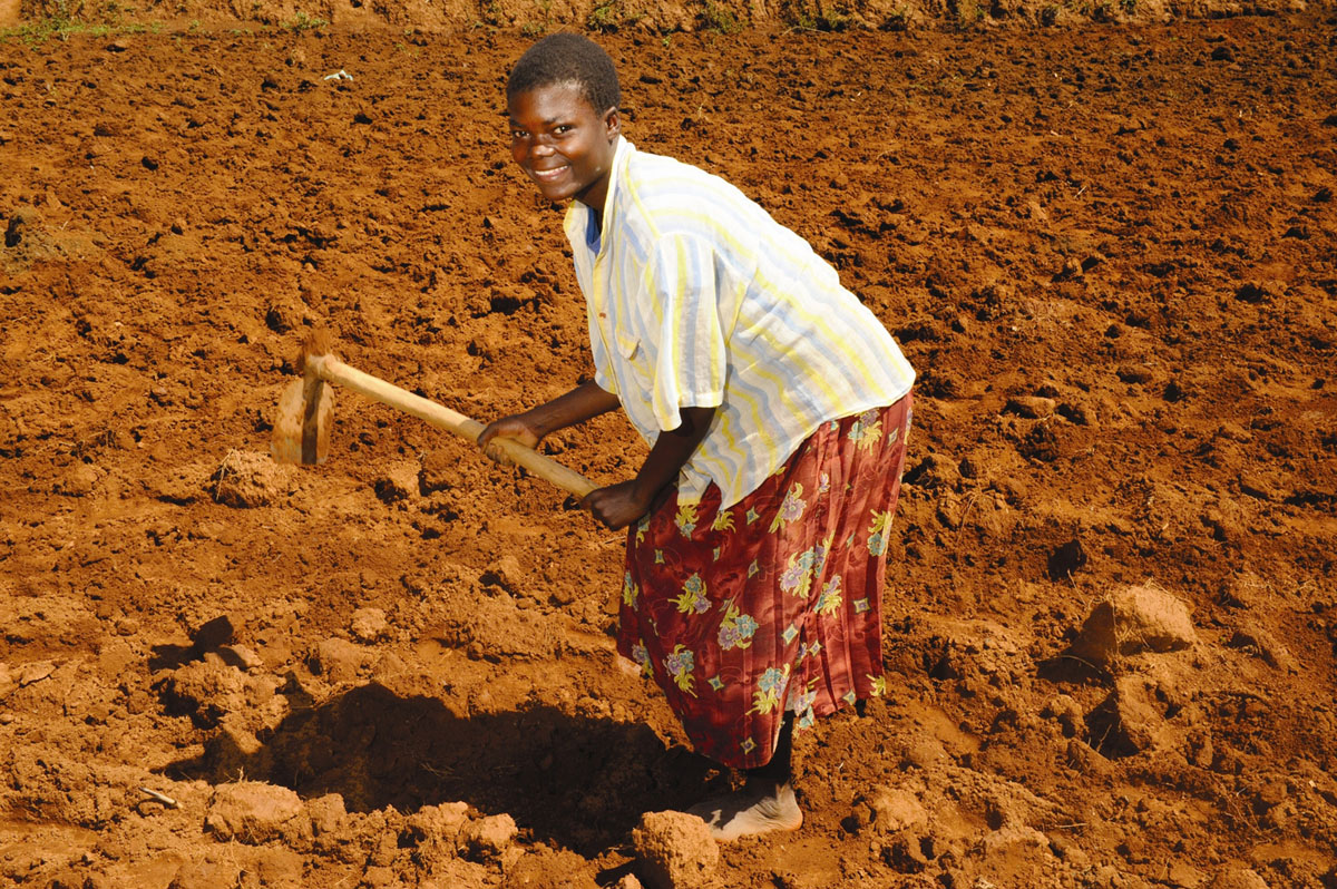 African woman smiles at the camera as she hoes reddish-brown soil