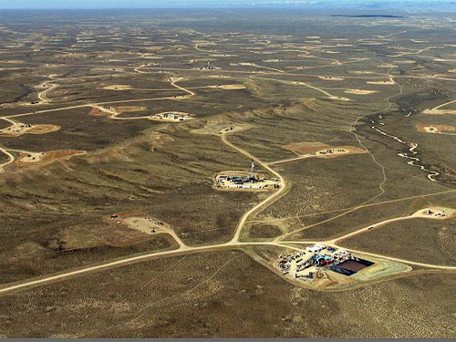 Aerial of vast, dry and brown land densely dotted with drill sites connected by dirt roads